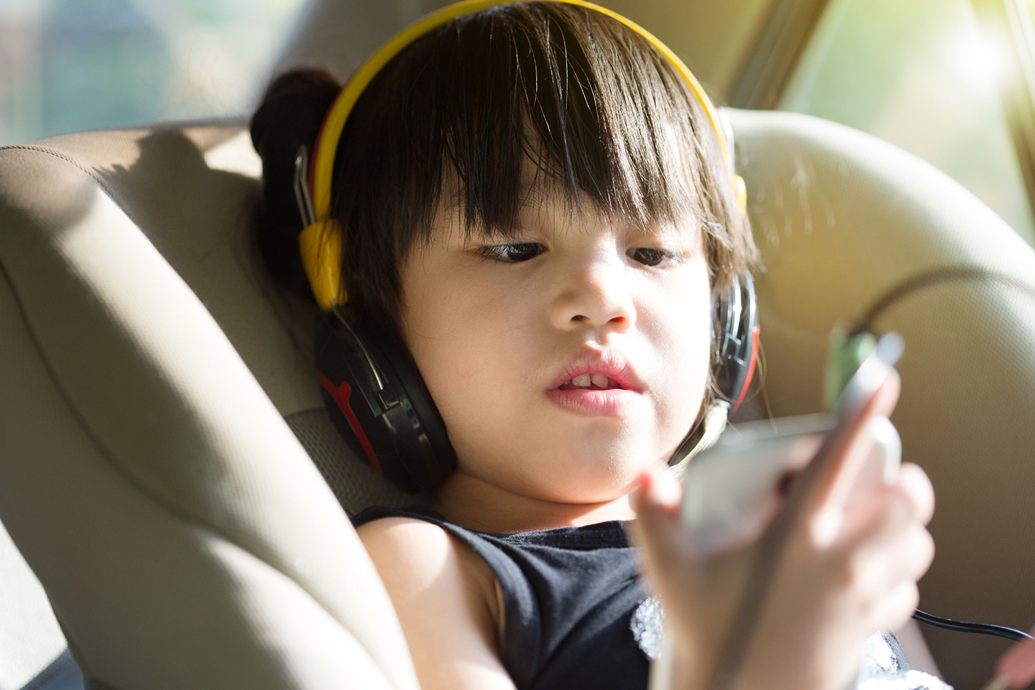 Young boy in car seat listens to a program on his mobile phone.