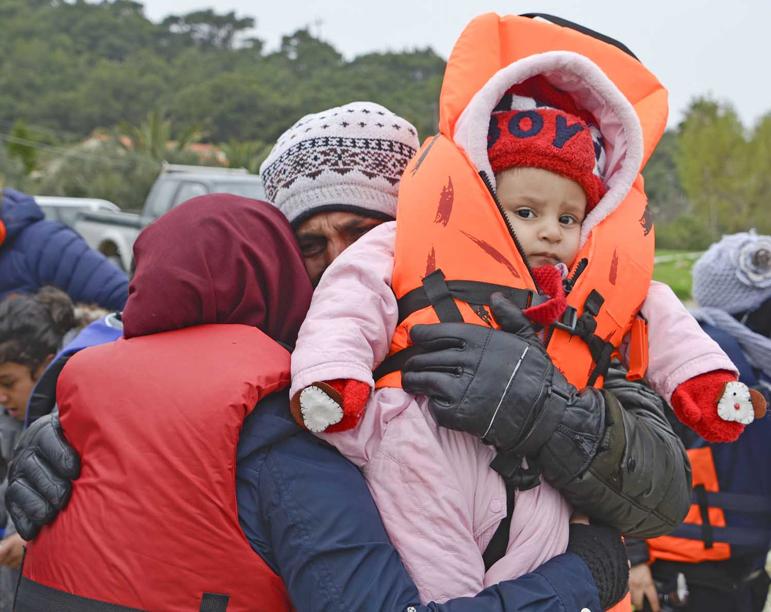 Refugee parents embrace their baby boy after upon arrival at Lesvos, Greece, after fleeing from their home country.