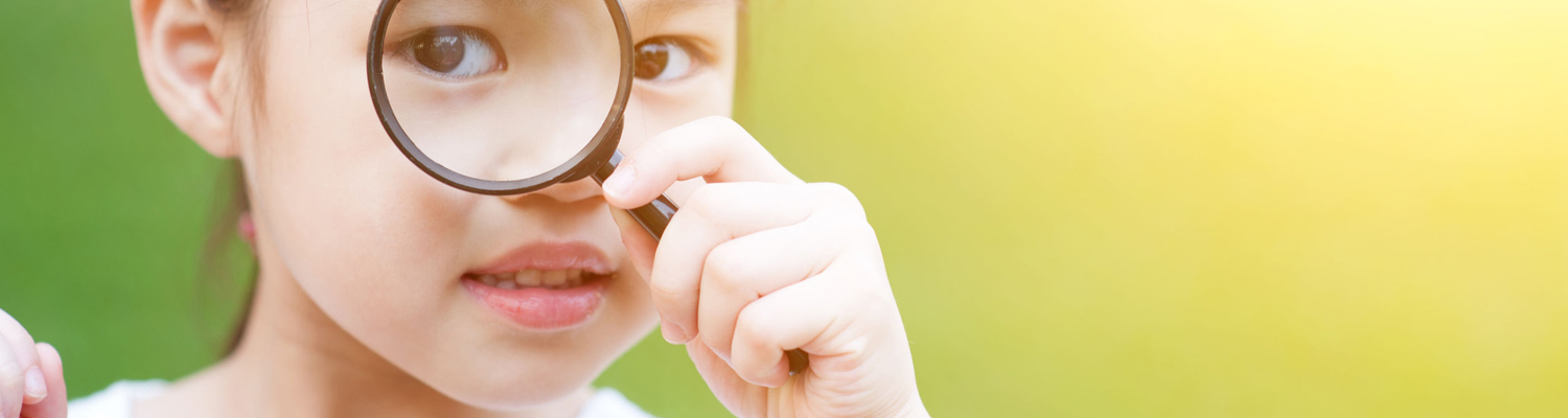 Little girl exploring nature by magnifier.
