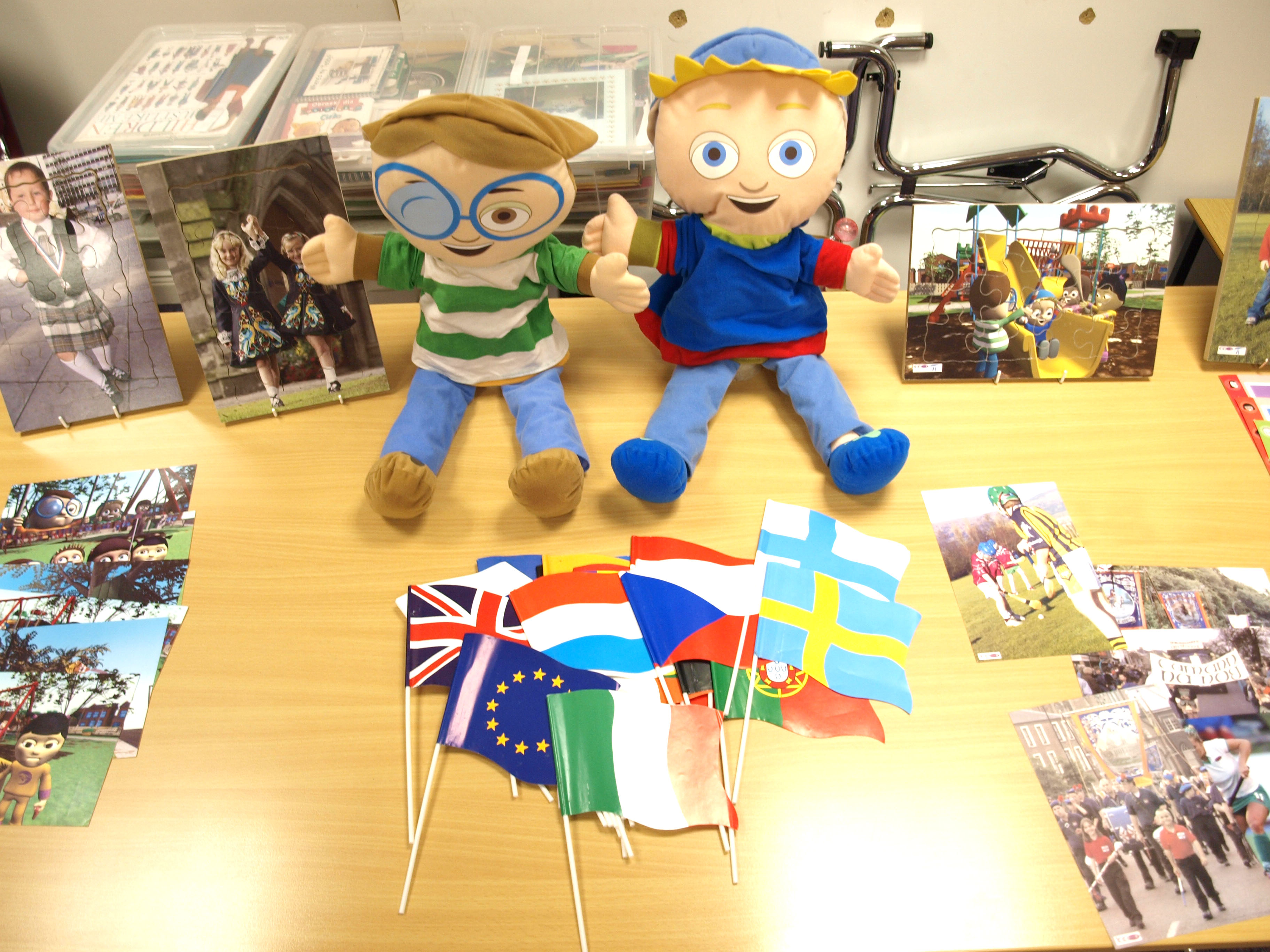 Two happy puppets sit upon on a desk with photographs - The Media Initiative for Children (N. Ireland).