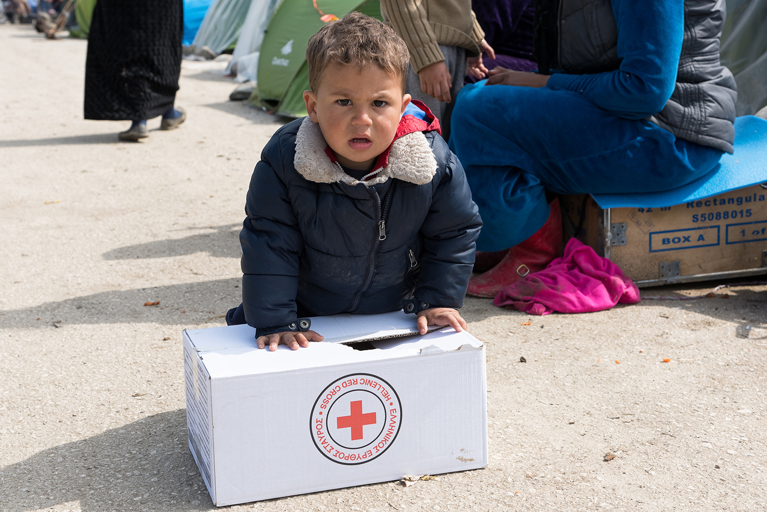 Worried young boy in refugee camp leans on Red Cross relief box.