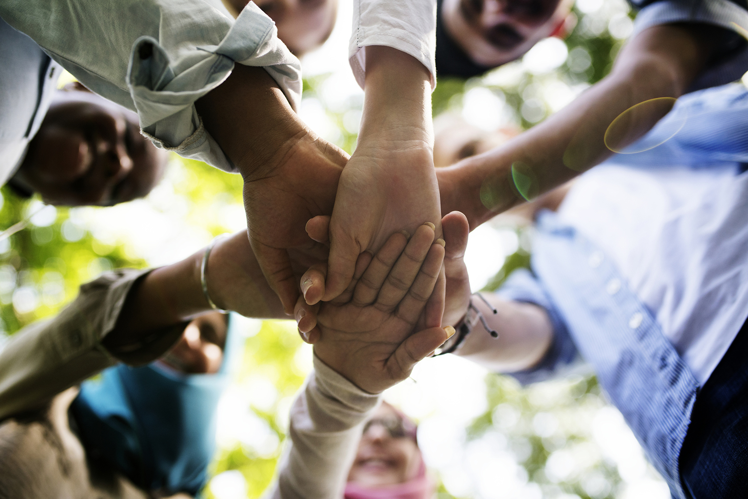 Team of young adults engage in a hand huddle.
