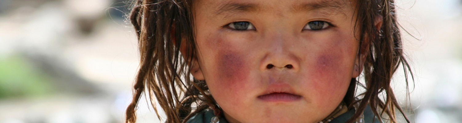 A lovely little Tibetan girl with plateau-red cheeks. © Yue Liu | Dreamstime Images