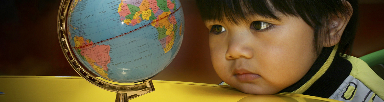 A curious young Asian child gazes at a globe. © Gilbert Agao | Dreamstime Images