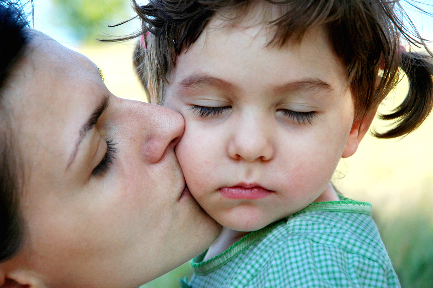 Mother kisses her sleepy daughter on the cheek.