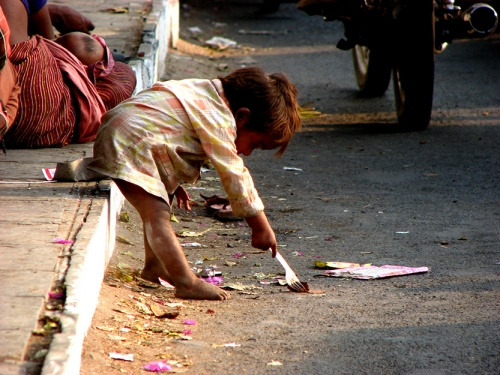 Homeless child searching for food on the side of a street. © Nikhil Gangavane, Dreamstime Images