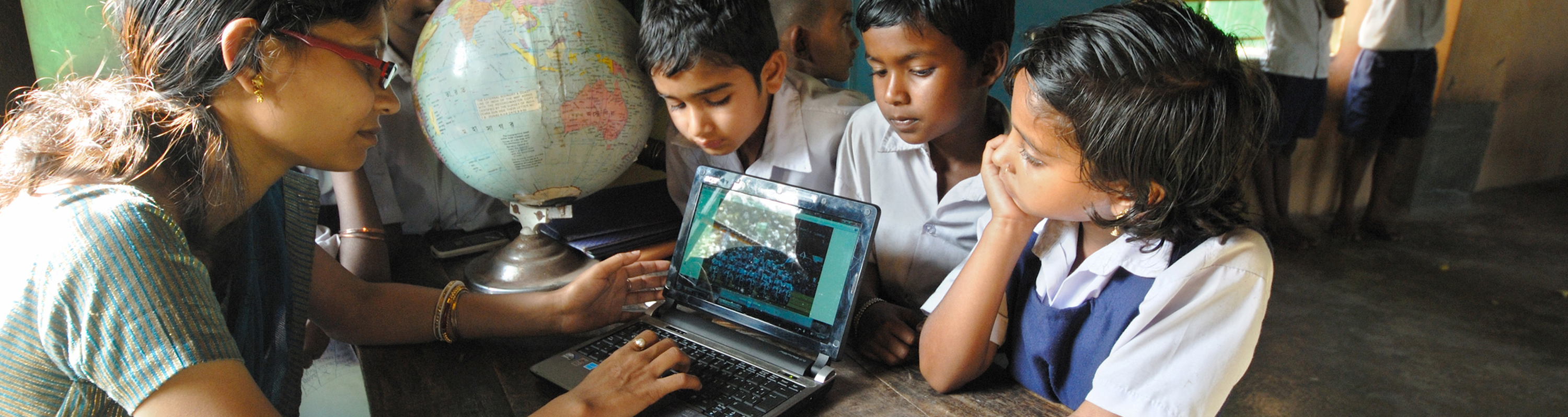 School teacher teachers her students with the help of a laptop at the rural school (West Bengal, India). © Samrat35 | Dreamstime Images