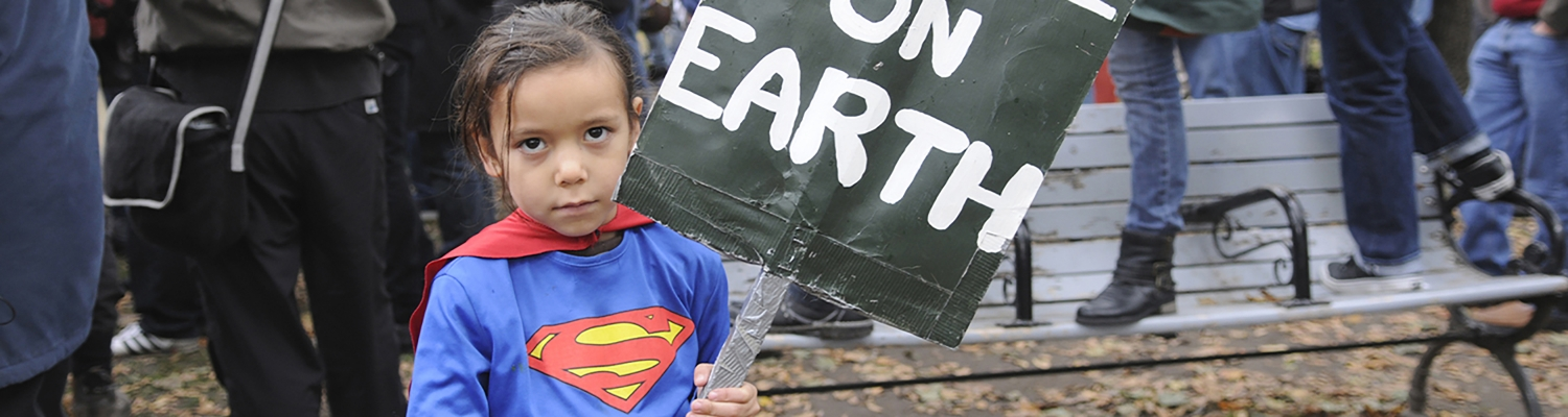 "Young boy wearing superman costume holds a ""Peace on Earth"" sign (Toronto, Canada). © Arindam Banerjee 
