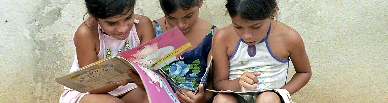 Three school girls read yet colorful childrens books with lots of pictures, drawings (State of Bahia in the North-East region, Brazil). © Sjors737 | Dreamstime Images