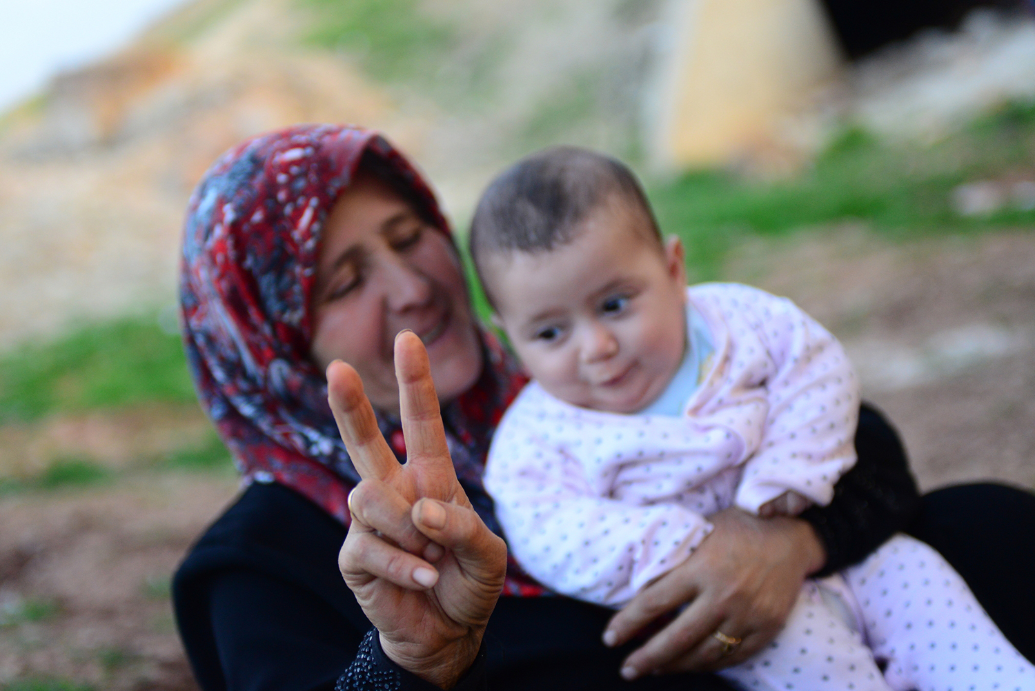 Syrian refugee mother with baby holds a hand peace sign.