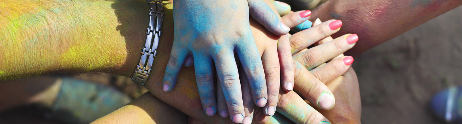 Friends at a Holi colors festival (India) join hands as a show of unity and teamwork. © Darya Petrenko   Dreamstime Images
