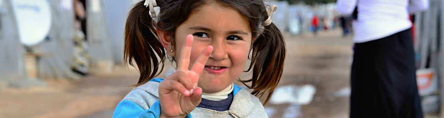 Syrian girl in refugee camp (Suruc, Turkey) holds peace hand sign.