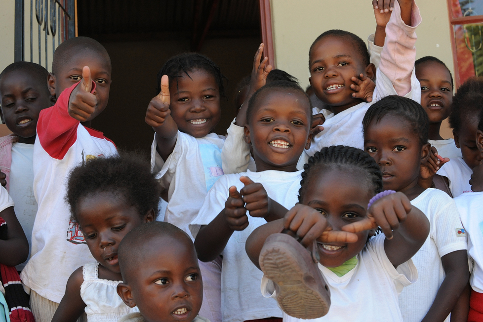 Refugee school children in South Africa give thumbs up.
