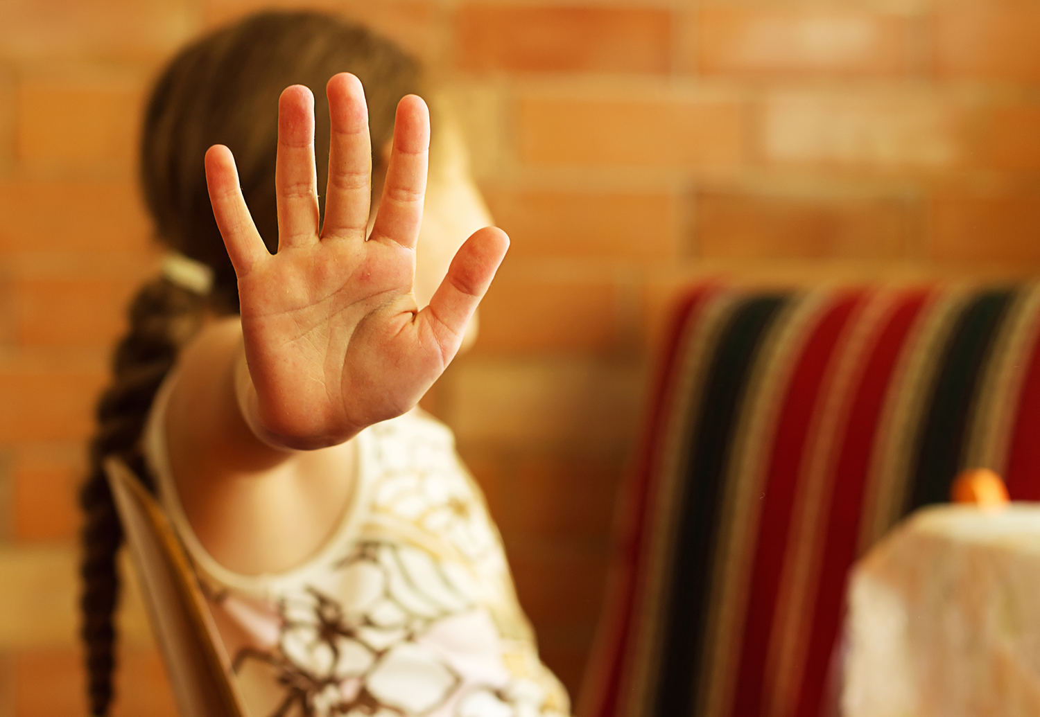 Young girl looks away as she holds up her hand to stop childhood violence.