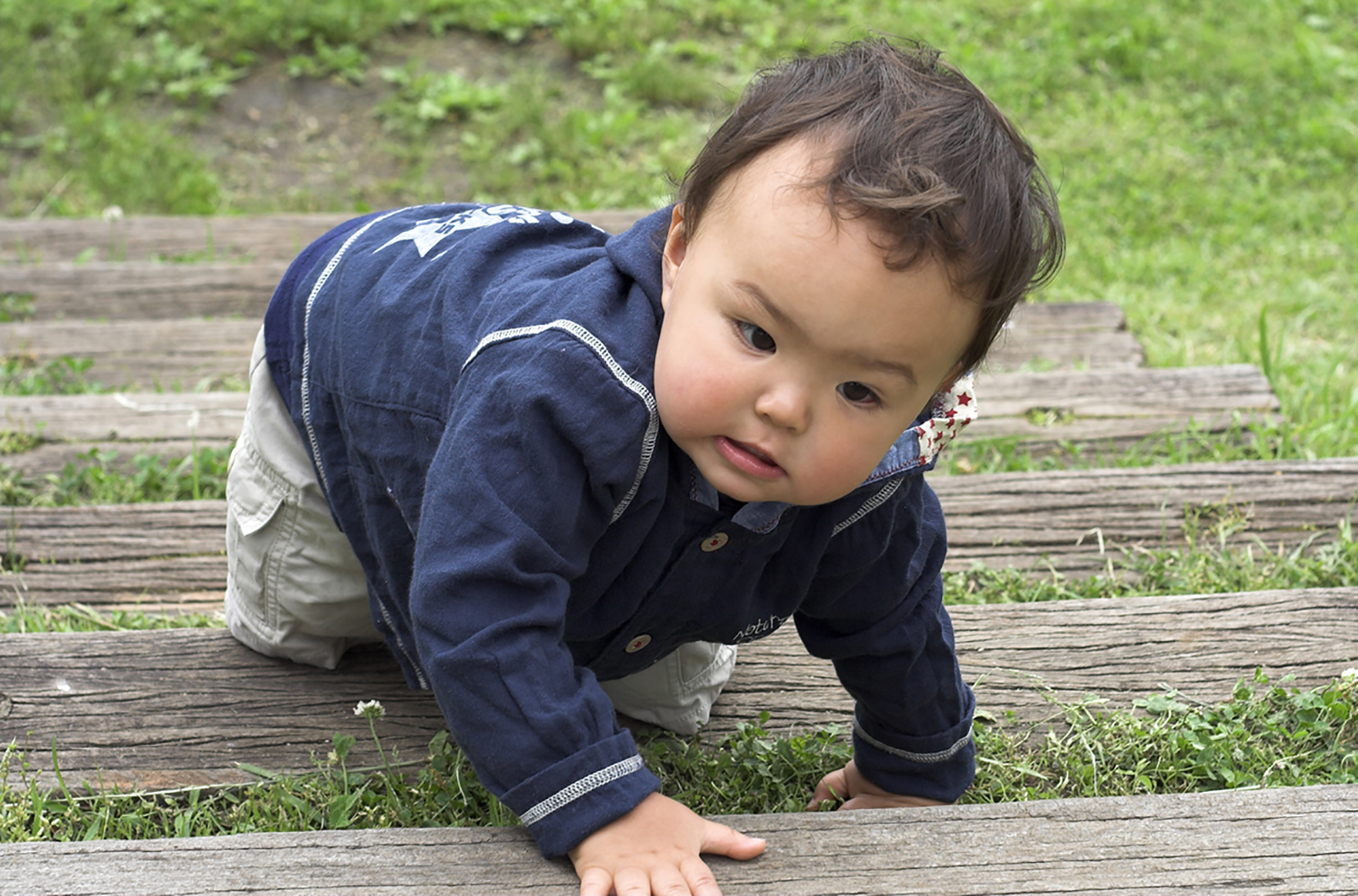 Asian toddler climbing up outdoor wooden stairs.