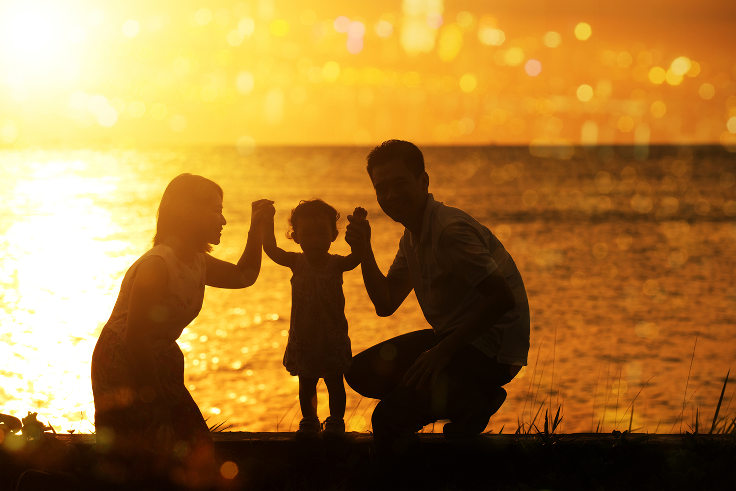 Mother and father share a bonding experience with their young child by holding hands on an ocean beach at sunset.