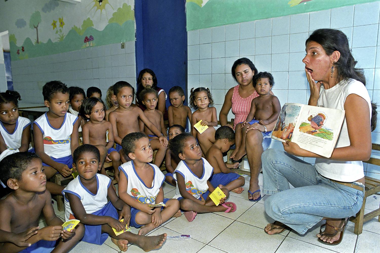 Teacher reads from storybook to school children (Brazil).