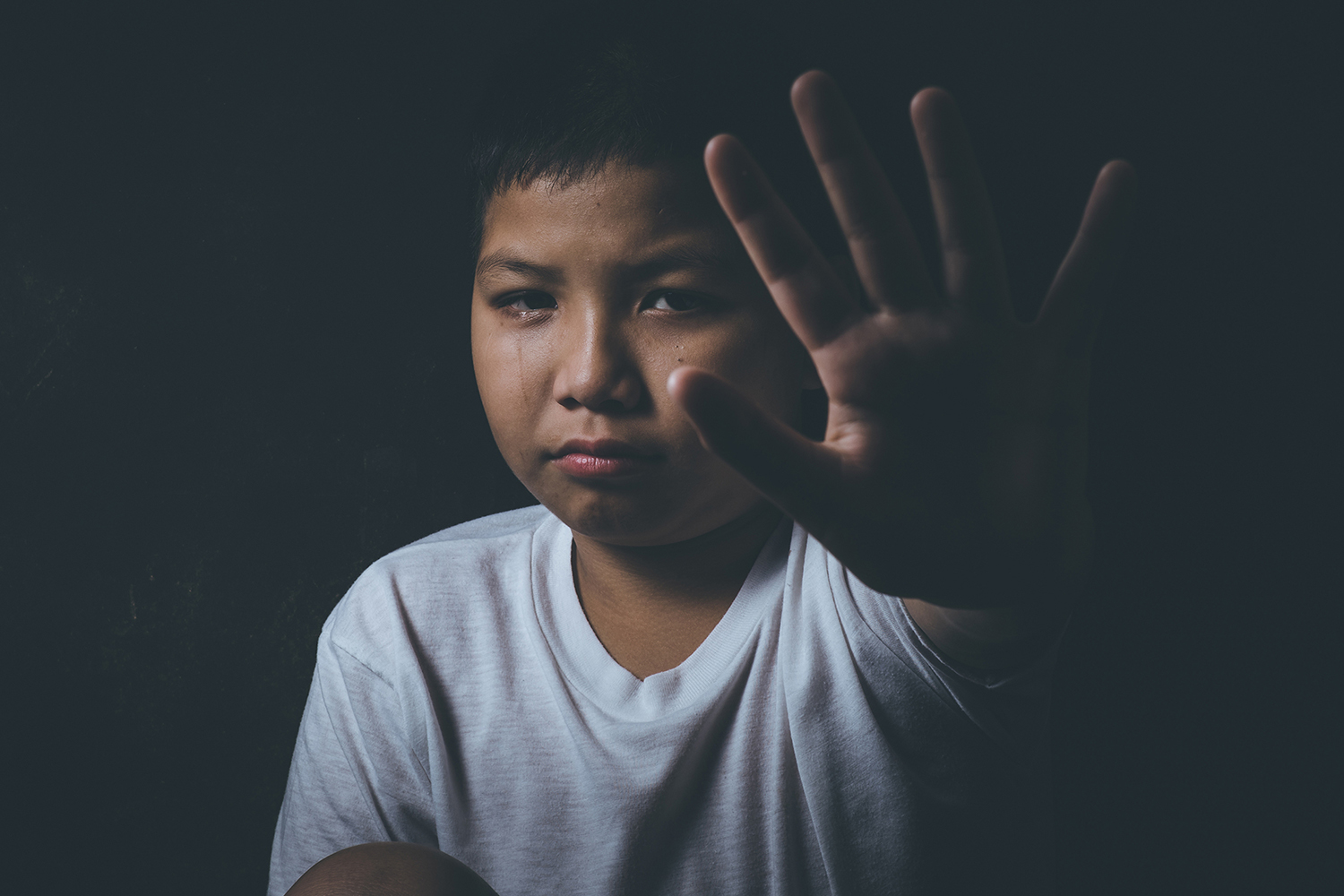 "Asian boy at high risk of being bullied, trafficked and abused signals ""Stop"" with his hand."