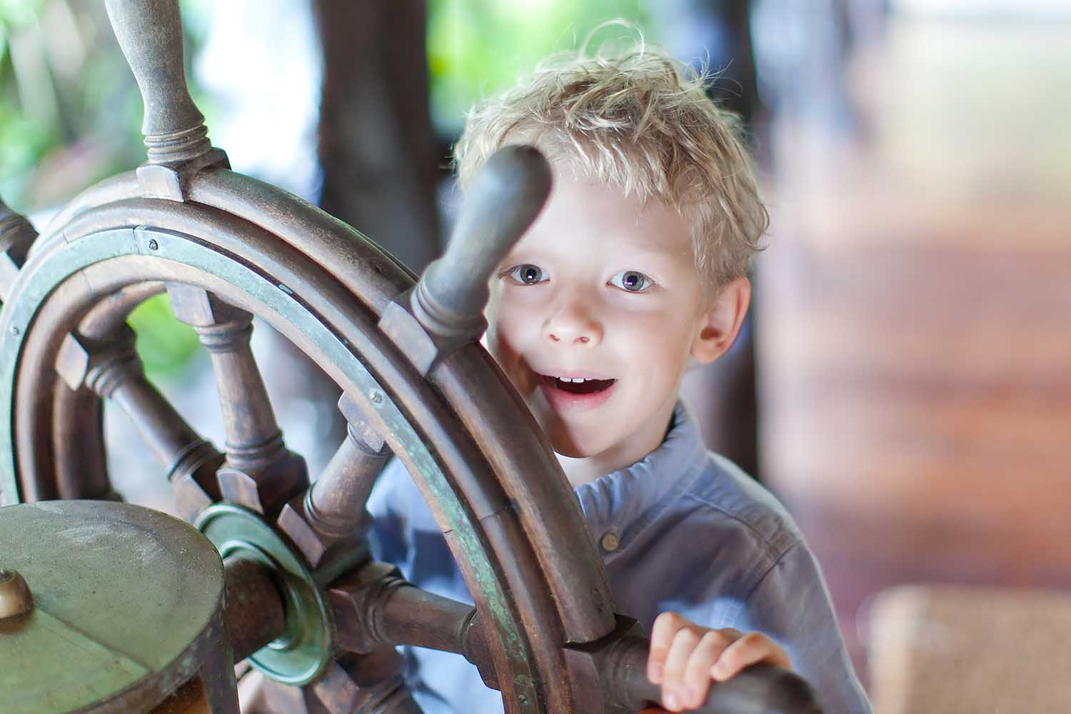 Happy boy guides a ship's steering wheel.