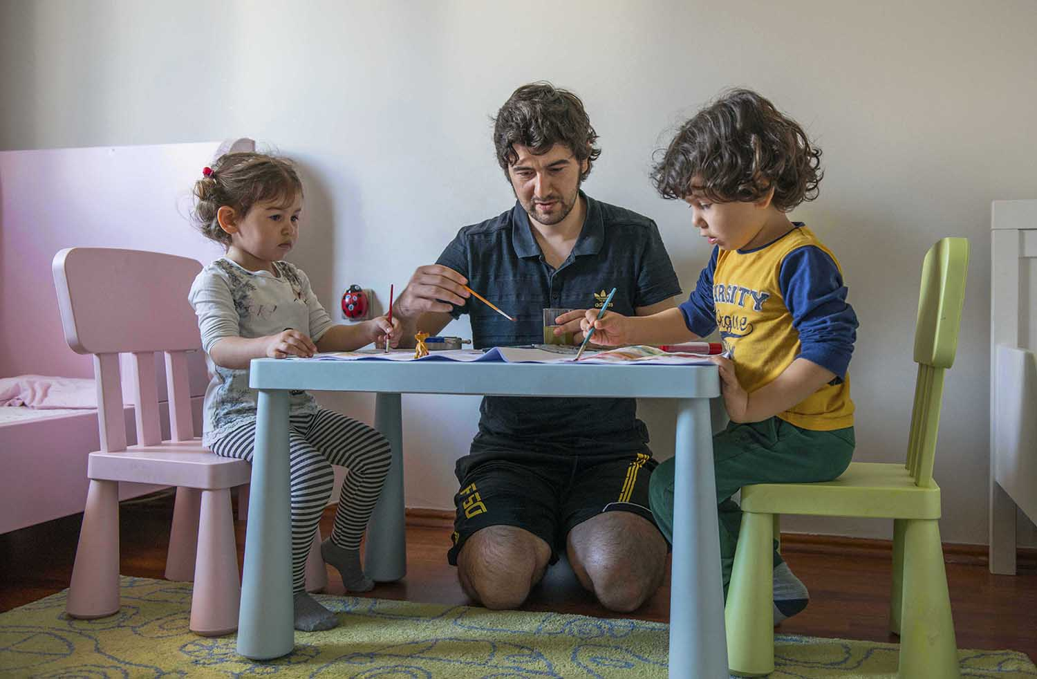 Father and his two children engage in artwork (Turkey).