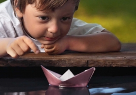 Young boy launches paper ship in a pool of water.