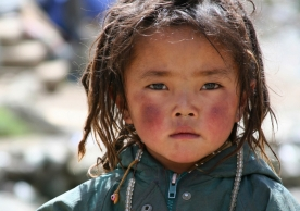 A lovely little Tibetan girl with plateau-red cheeks.