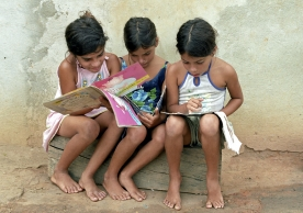 Three school girls read yet colorful childrens books with lots of pictures, drawings (State of Bahia in the North-East region, Brazil).