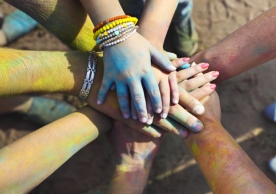 Friends at a Holi colors festival (India) join hands as a show of unity and teamwork.