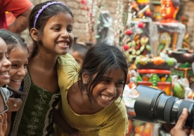 East Indian girls on a city street are enjoying being photographed.