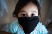 Portrait of Asian toddler girl wearing black fabric mask for protection from Covid-19. © ellinnur / 123rf images.