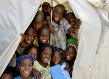 Happy African school children show their support for UNICEFs PBEA program.
