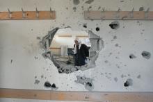 Muslim girl walks through war damaged school building.
