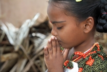 East Indian girl holds her hands together in prayer.