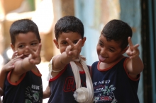Smiling refugee boys hold hand peace signs.