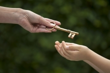 Mother hands shiny brass key to her young daughter.