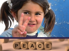 Smiling Syrian refugee girl in pigtails holds hand peace sign (Turkey).