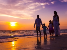Mother, father, daughter and son share a bonding experience while walking along the oceanside at sunset holding hands.