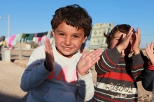 Two Syrian Kurd refugee boys happily clap their hands (Municipality of Suruc Tent City).