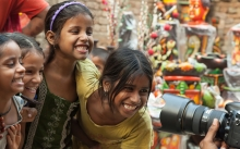 Happy East Indian girls pose for photographer on city street.