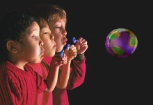 Three multi-racial children blow a single bubble with earth's reflection.