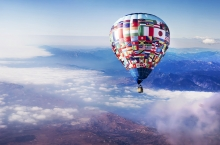 UN multi-flag decorated hot air balloon sails in a blue sky above the clouds.