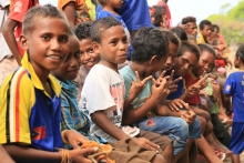 Timor Leste children sitting together hold hand peace signs.