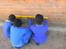 African school boys measure the dimensions of a brick wall.