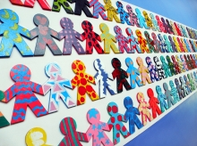 Multi-colored cutouts of children holding hands, symbolizing the diversity and unity of the world's people.