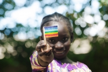 Young African girl from Mali holds small rainbow colored flag of peace.