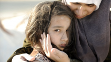 Syrian refugee mother comforts her frightened daughter.