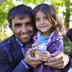 Hopeful refugee father holds his young daughter (Serbian - Croatina border).